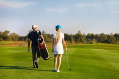 Couple playing golf on a golf course walking to the next hole Royalty Free Stock Images