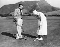 Couple playing golf together royalty free stock photos