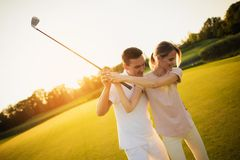 Couple playing golf together at sunset, swinging together to hit the ball with a golf club. Couple playing golf together. A men is teaching a women to play golf stock photo