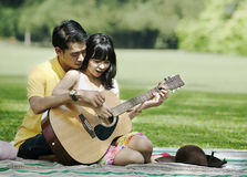 Couple playing guitar. Romentic young couple playing guitar in the park Royalty Free Stock Photos