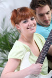 Couple playing the guitar Stock Photography