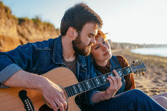 Couple playing guitar on beach. Young caucasian couple playing guitar on beach during sunset or sunrise Stock Images