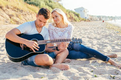 Couple playing guitar on beach Stock Photos