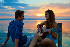 Couple playing guitar in sunset pier at dusk beach Royalty Free Stock Image