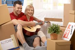 Couple playing guitar together in new house Stock Photo