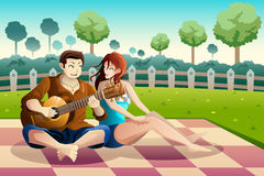 Couple playing guitar together in a park Royalty Free Stock Photo