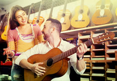 Couple playing guitars in music shop Stock Photos