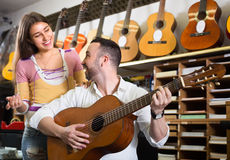 Couple playing guitars in music shop Stock Photo