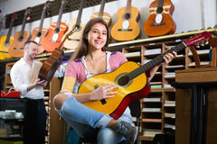 Couple playing guitars in music shop Royalty Free Stock Image