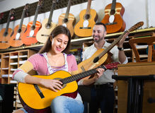Couple playing guitars in music shop Stock Image
