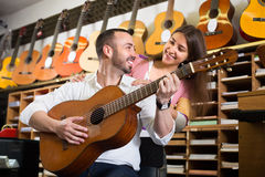 Couple playing guitars in music shop Royalty Free Stock Photography