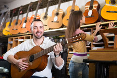 Couple playing guitars in music shop Stock Images