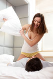 Couple Playing and Having a Pillow Fight in Bed Royalty Free Stock Image