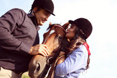 Couple playing with a horse Stock Photos