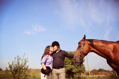 Couple playing with a horse Royalty Free Stock Image