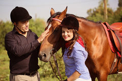 Couple playing with a horse Royalty Free Stock Photography