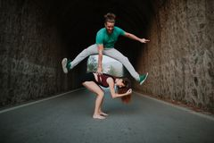 Man leapfrog jumping over woman on a road. Couple playing leapfrog jumping in a tunnel Royalty Free Stock Images