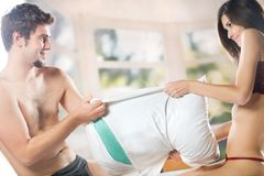 Couple playing with  pillow on the bed in bedroom Royalty Free Stock Photo