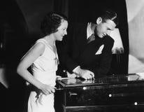 Couple playing with pinball machine Stock Photos