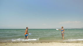 Couple playing ping pong on the beach. Slow motion of happy couple splashing water with paddles and playing tennis in water with ping pong rackets. Man falling stock footage
