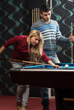 Couple Playing Pool At The Bar Royalty Free Stock Photos