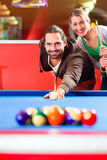Couple playing pool billiard game Stock Photography