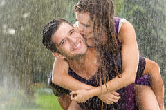 Couple playing in the rain. Couple in love playing in the summer rain Royalty Free Stock Photo