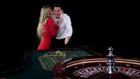 Couple playing roulette is eager to win at the gambling house. Black. Couple playing roulette is eager to win at the gambling house, young couple celebrating win stock video footage