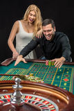 Couple playing roulette wins at the casino. Couple playing roulette wins at the casino, gambling chips taken by hands Royalty Free Stock Photos
