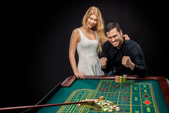 Couple playing roulette wins at the casino. Couple playing roulette wins at the casino, gambling chips taken by hands Royalty Free Stock Photography