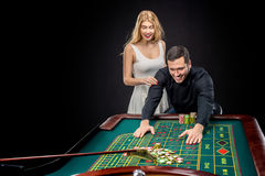 Couple playing roulette wins at the casino. Couple playing roulette wins at the casino, gambling chips taken by hands Stock Photos