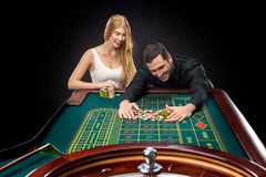 Couple playing roulette wins at the casino. Couple playing roulette wins at the casino, gambling chips taken by hands man Stock Photography