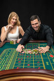 Couple playing roulette wins at the casino. Couple playing roulette wins at the casino, gambling chips taken by hands men Stock Images