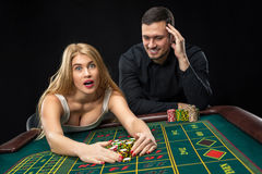 Couple playing roulette wins at the casino. Couple playing roulette wins at the casino, gambling chips taken by hands woman Stock Photos