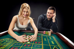 Couple playing roulette wins at the casino. Couple playing roulette wins at the casino, gambling chips taken by hands woman Stock Images