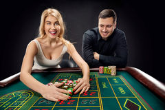 Couple playing roulette wins at the casino. Couple playing roulette wins at the casino, gambling chips taken by hands woman Royalty Free Stock Image
