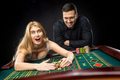 Couple playing roulette wins at the casino. Couple playing roulette wins at the casino, gambling chips taken by hands woman Royalty Free Stock Photography