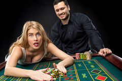 Couple playing roulette wins at the casino. Couple playing roulette wins at the casino, gambling chips taken by hands woman Stock Photography