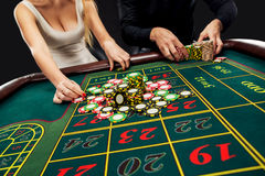 Couple playing roulette wins at the casino. Couple playing roulette wins at the casino, gambling chips taken by hands woman. Closeup Royalty Free Stock Photo