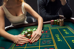 Couple playing roulette wins at the casino. Couple playing roulette wins at the casino, gambling chips taken by hands woman. Closeup Stock Photo
