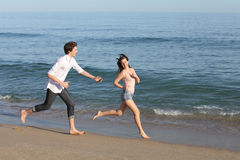 Couple playing and running on the beach Royalty Free Stock Photo
