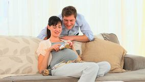 Couple playing with shoes of their future baby Royalty Free Stock Photo