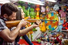 Couple playing shooting games while visiting an amusement park. Young men holding gun and shooting stock photos