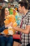 Couple playing shooting games. Young couple playing shooting games while visiting an amusement park stock image