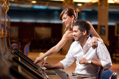 Couple playing the slot machine
