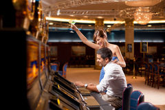 Couple playing the slot machine. Young couple winning at slot machine Stock Photos