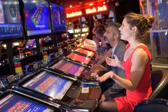 Couple playing at slot machines in casino Royalty Free Stock Photography