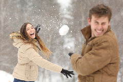 Couple playing with snow and girlfriend throwing a ball. In winter holidays stock photography