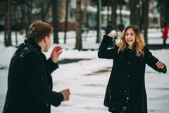 Couple playing with snow and girlfriend throwing a ball in winter holidays. Happy Stock Images