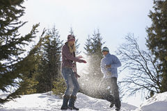 Couple Playing In Snow On Hill Royalty Free Stock Photography